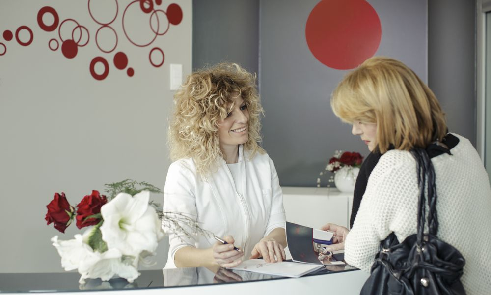 Receptionist and patient talking.