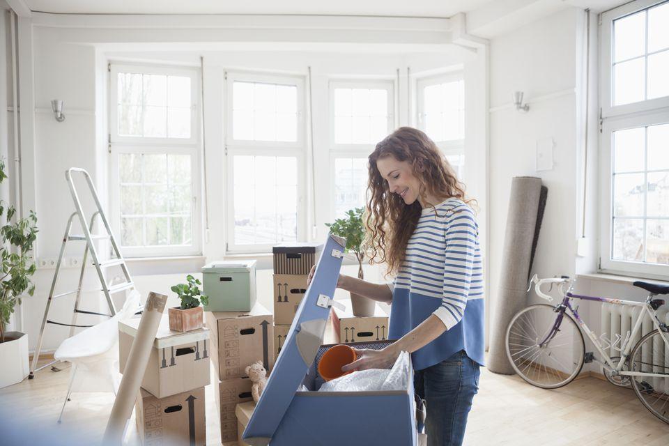 Woman in new apartment unpacking cardboard box