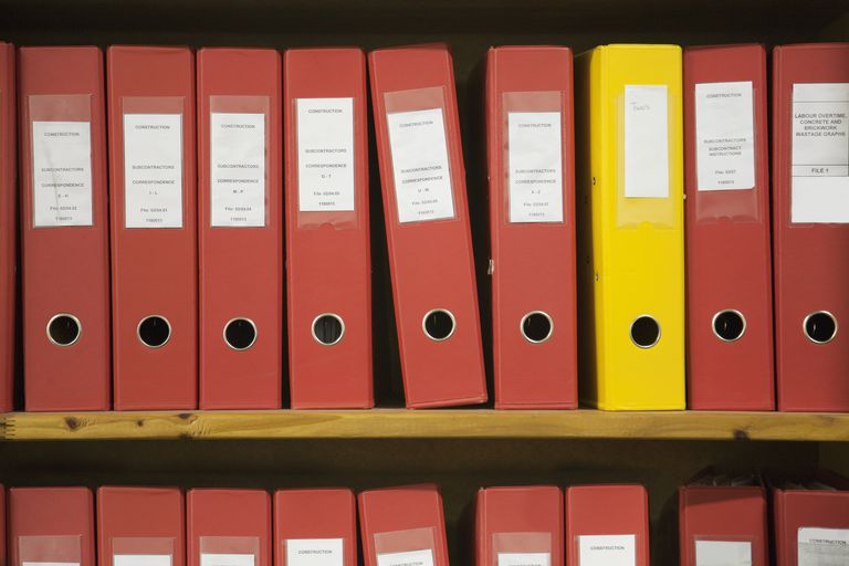 Row of red work files, with one yellow one