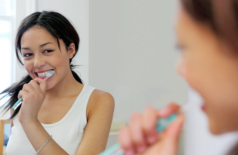 Teen brushing teeth