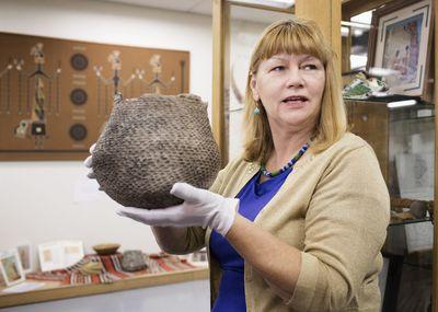 Caucasian curator holding artifact in museum