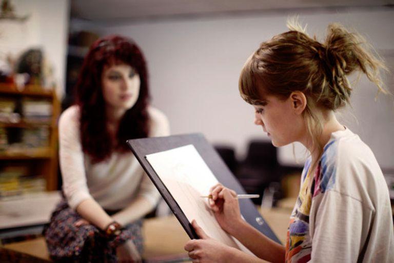 Young woman in art class sketching life model