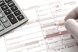 person filling out irs 1099 tax form