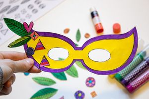 A yellow and purple paper Mardi Gras mask