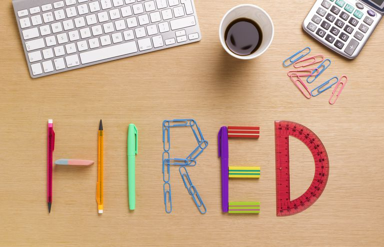 Hired spelled out in office supplies on desk