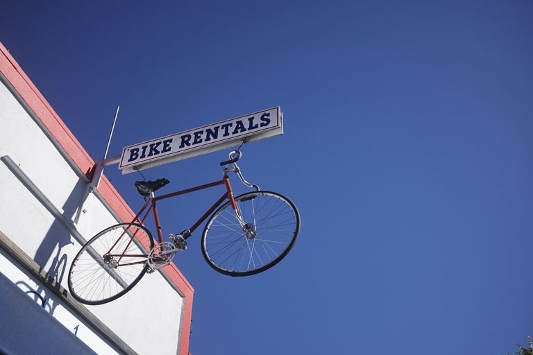 Bicycle sign for bike rental against blue sky, California, USA