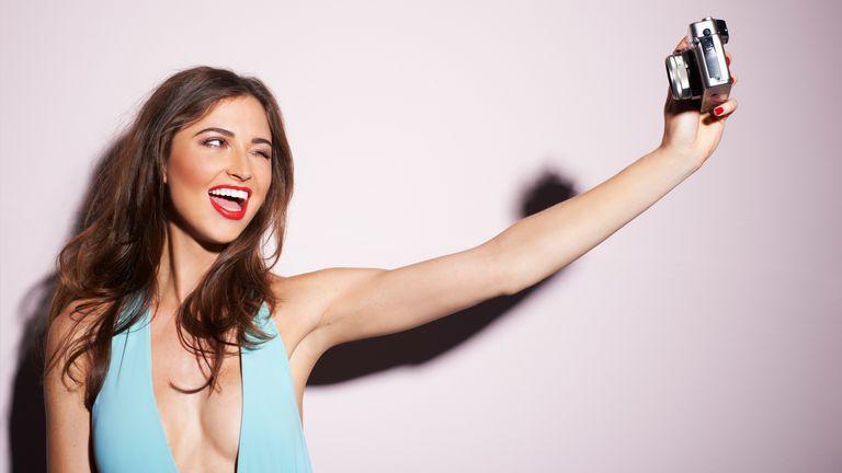 Beautiful woman in a blue dress taking a selfie