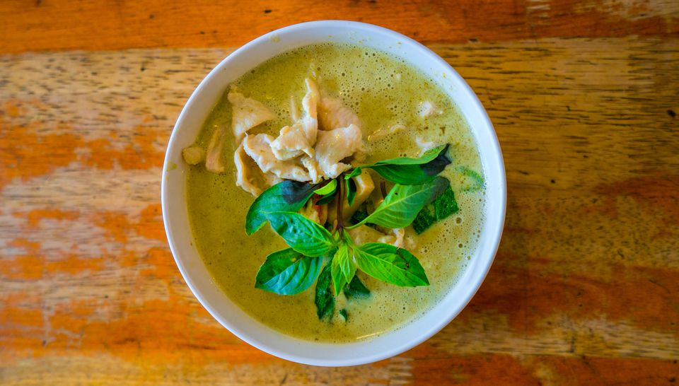 Thai green curry in a bowl on a wooden table