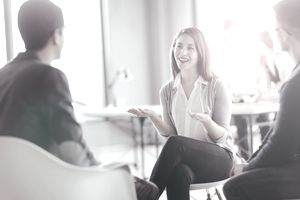 Woman talking to to men in a business setting