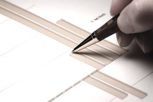 Graphs on paper and men using a pen to review them