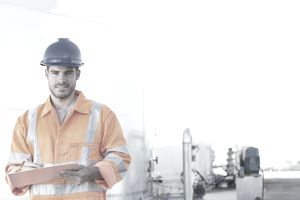 Portrait of worker with clipboard near silage storage towers
