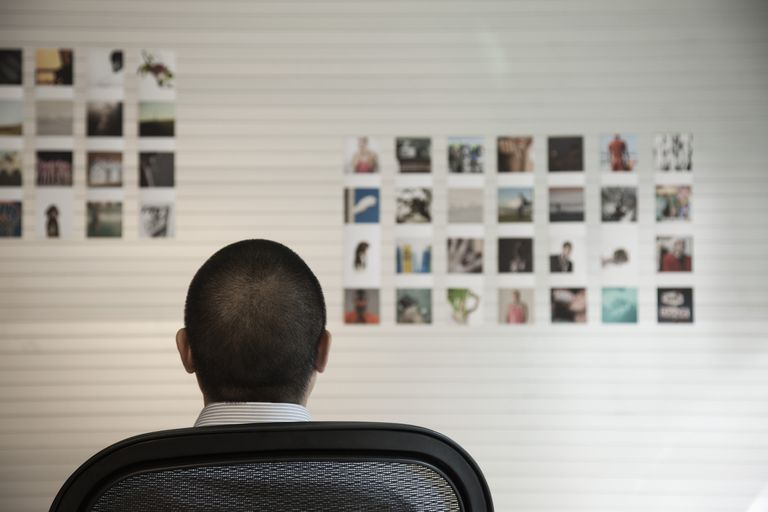 man looking at photographs on wall in office