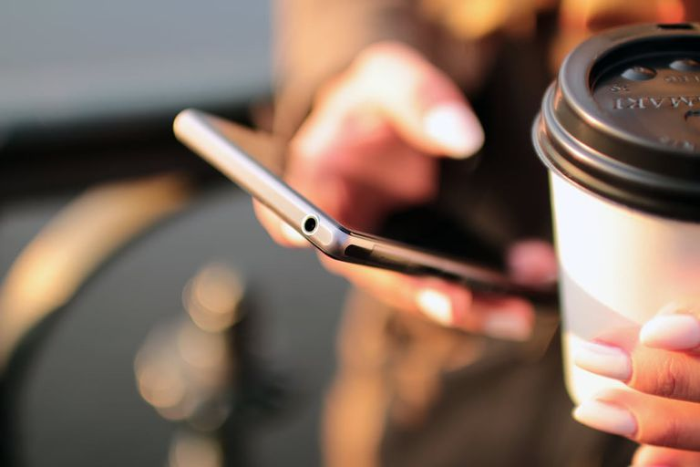 woman with smartphone and coffee in hand