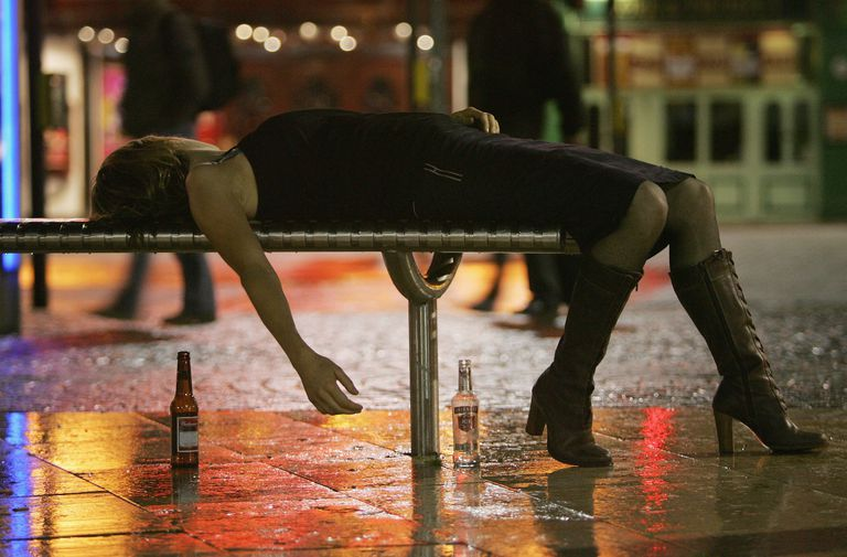 woman passed out on a bench with beer