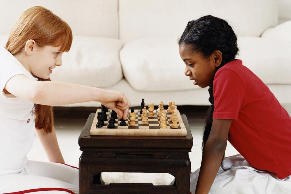 Two Girls Playing a Game of Chess in a Living Room