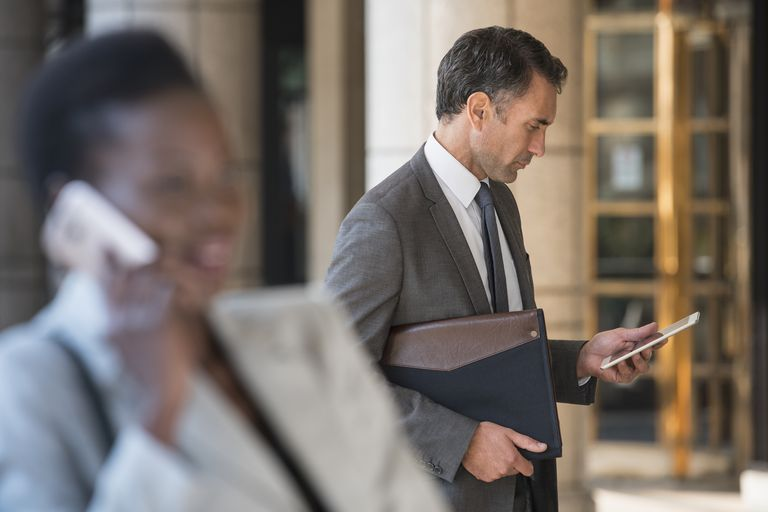 Corporate businessman using digital tablet outdoors