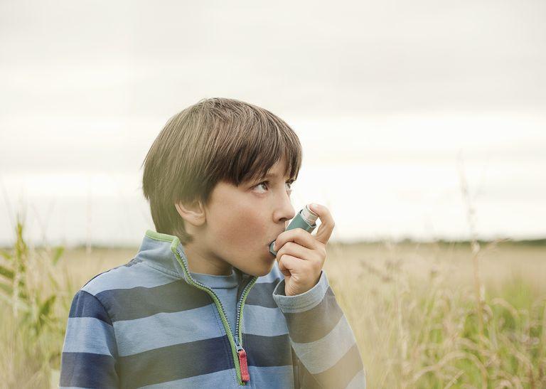 Anxious boy using an inhaler outdoors