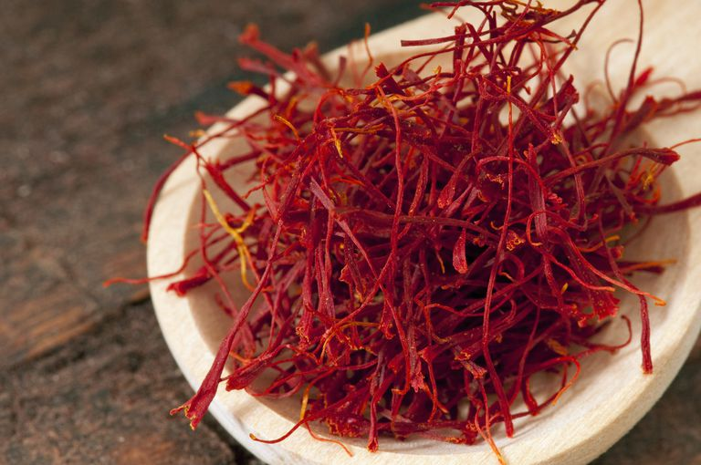 A wooden spoonful of bright red saffron