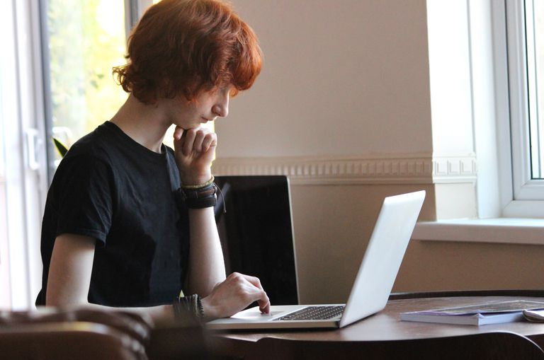 Image of boy surfing Internet on laptop-computer for school homework