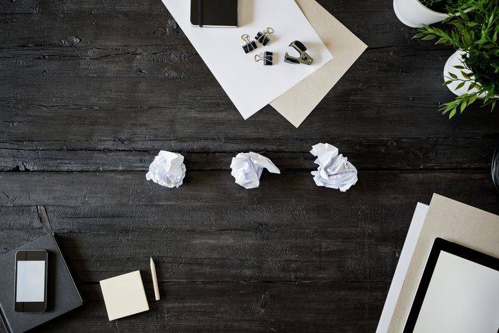Blank sheets of paper, pencil, smartphone and crumbled papers on black wood