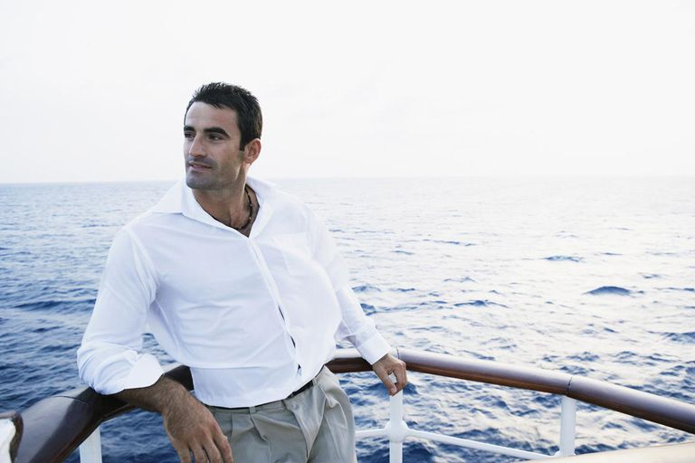 Mid adult man leaning against the railing of a ship