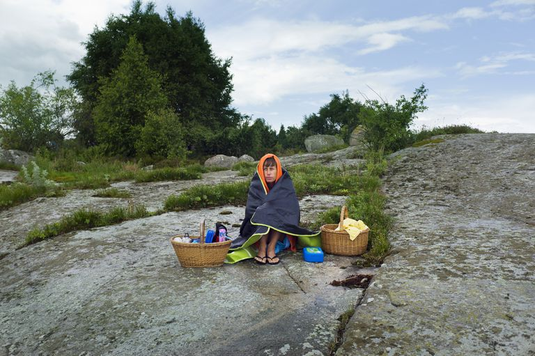 Man sitting on rock with picnic baskets
