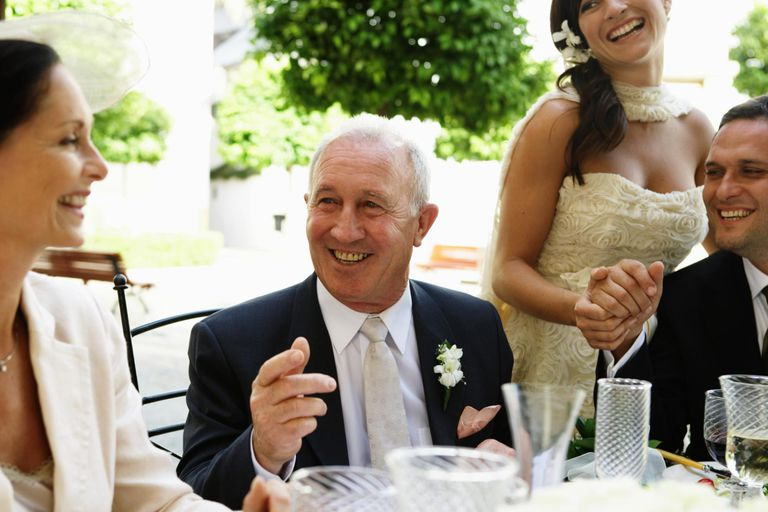 Bride and groom at table with parents, smiling