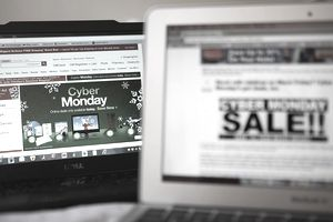 A photo of two computer screens with Cyber Monday advertisements on them.