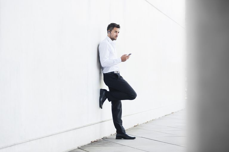 Young businessman leaning against wall texting on smartphone