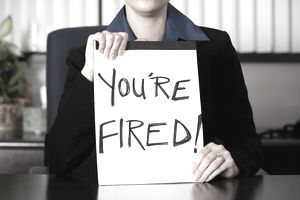 business woman holding sign that says you're fired