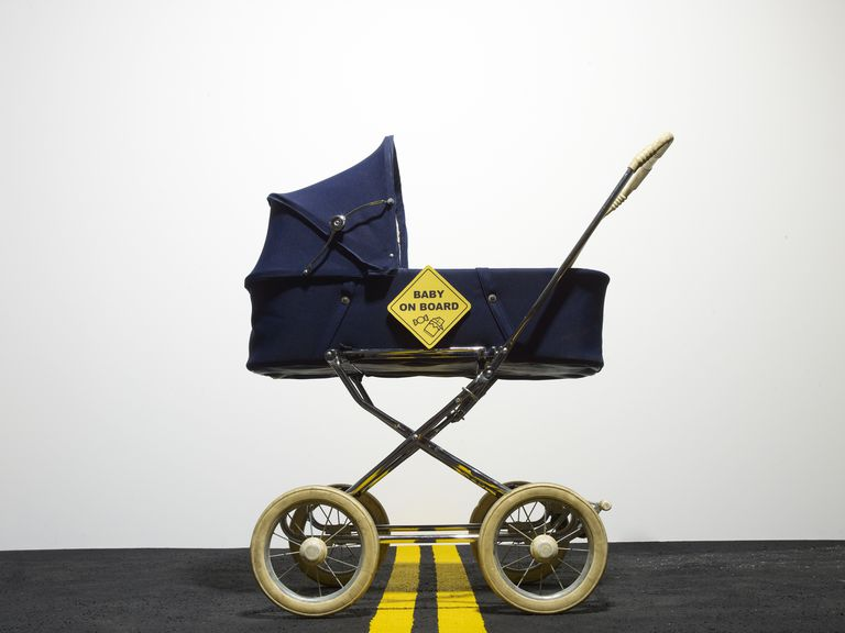 Vintage baby carriage with sign in the street