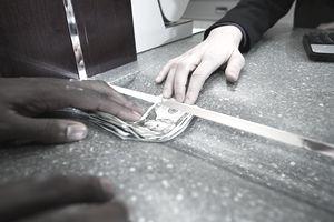 Teller handing cash to customer through security glass