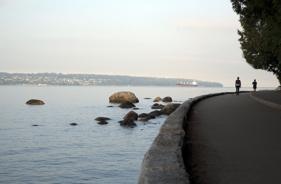 Exercising on the sea wall of Stanley Park with a view of tranquil English Bay, Vancouver, British Columbia, Canada