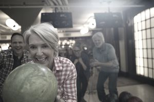 Enthusiastic woman with friends bowling at bowling alley