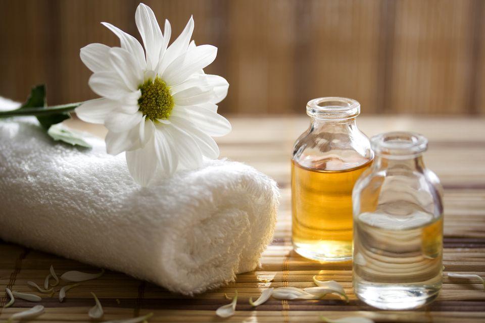 Essential oils next to a massage towel.