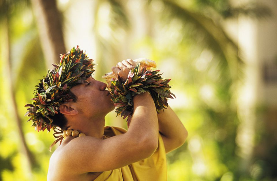 Hawaii, Oahu, Man blowing conch shell in Hawaiian dressings. Blurred background .