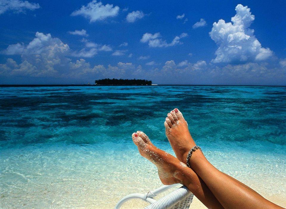 A picture of a woman with her feet up on the beach