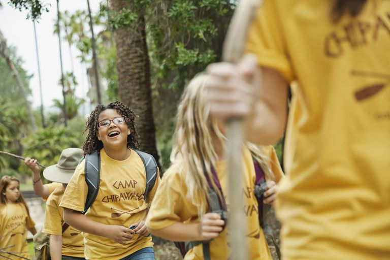 Little girl smiling while walking with friends and camp counsellor in forest