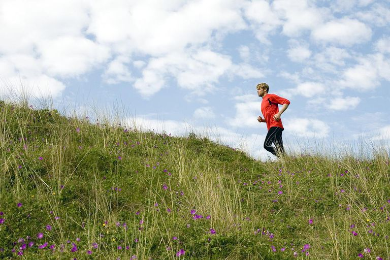 Man running up grassy hillside