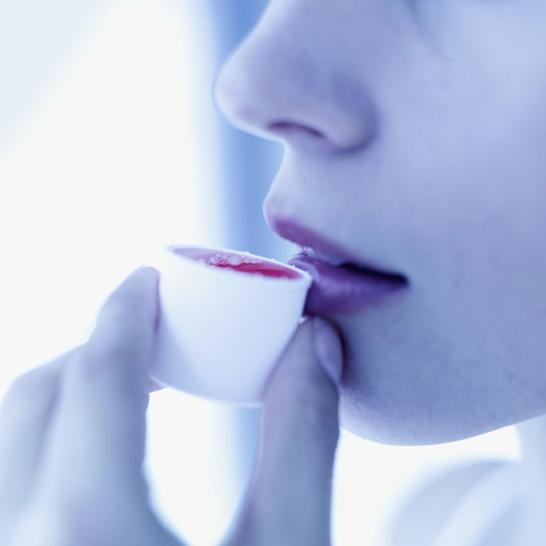 Close-up of young woman drinking mouthwash