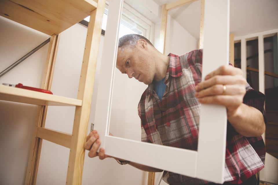 Mature man installing door for cabinet at home