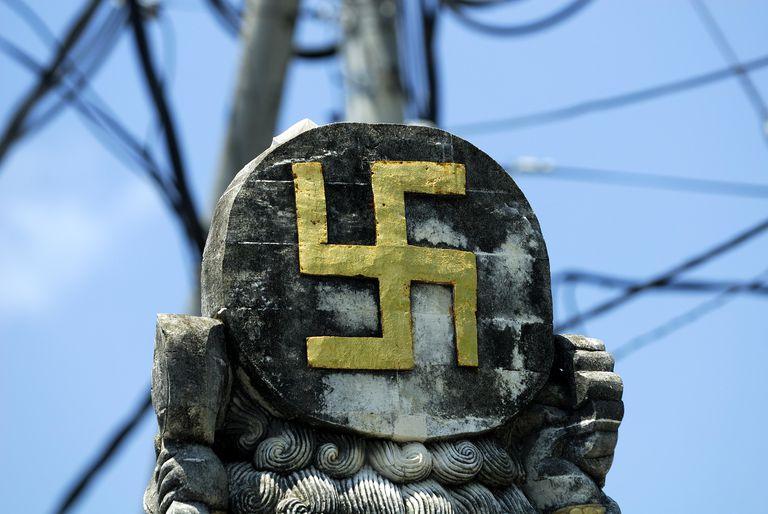 Ancient Hindu Symbol, the swastika, on statue at crossroads, Sanur, bali, Indonesia