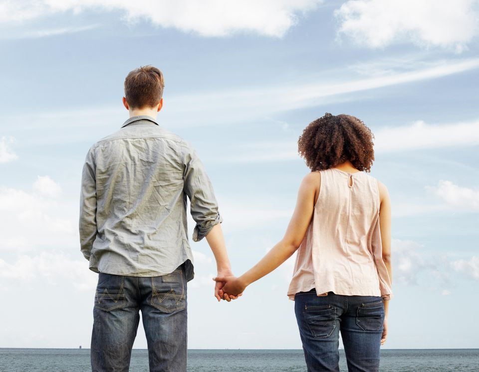 Young couple looking out to sea, holding hands
