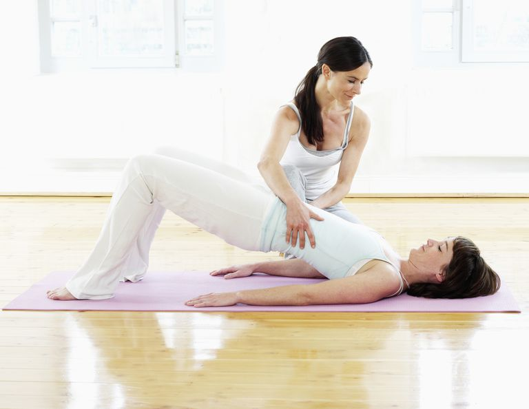 Yoga instructor working with woman