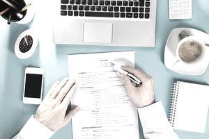 Businessman Reading Resume On Office Desk