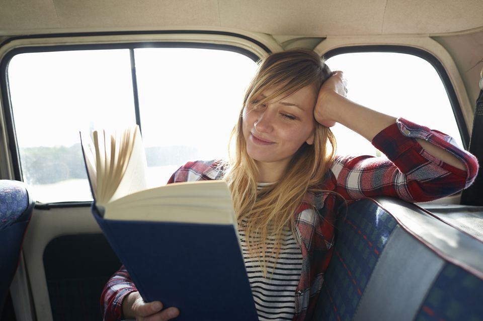 Woman reading book in car.