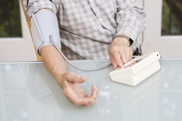 Senior Using Blood Pressure Gauge, Monitoring Healthcare Vitals at Home