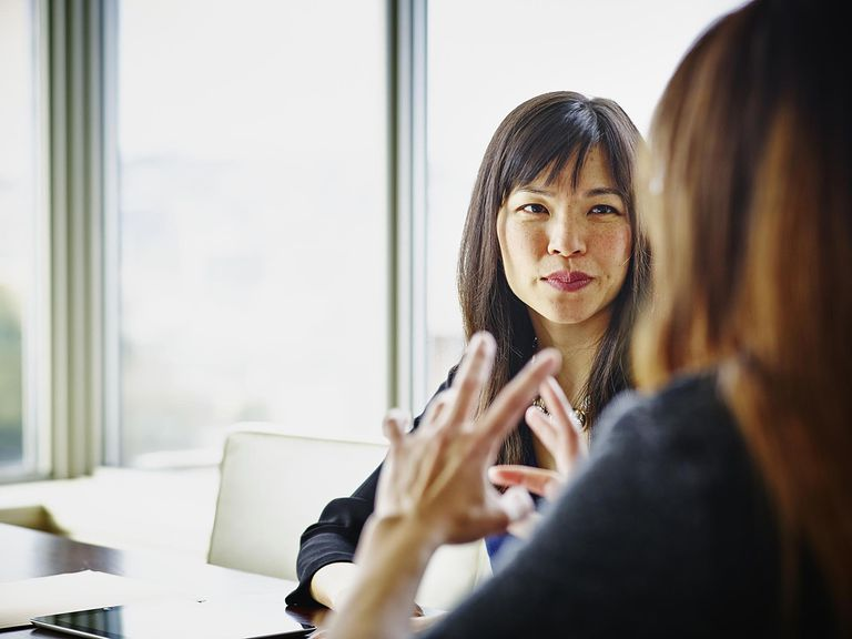 Two businesswomen discussing project details