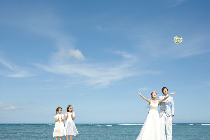 Newlywed couple throwing bouquet next to girls