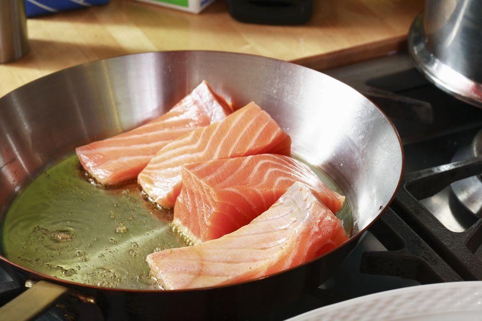 Fresh salmon frying in a pan